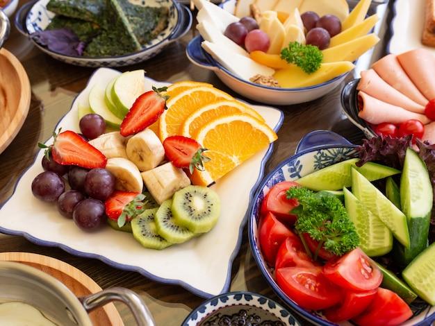 Vista laterale della frutta e delle verdure fresche sui piatti Foto Gratuite
