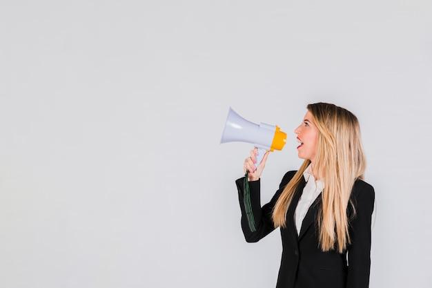 Vista laterale della giovane donna bionda che grida tramite il megafono contro il contesto grigio Foto Gratuite