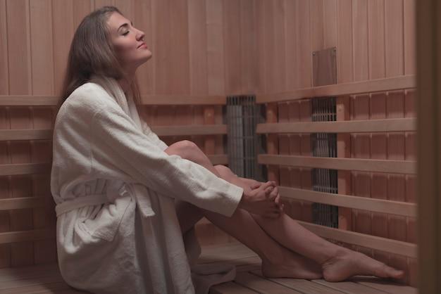 Vista laterale della giovane donna che si siede sul banco di legno nella sauna Foto Gratuite