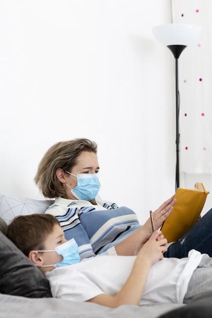 Vista laterale della madre e del bambino a letto indossando maschere mediche Foto Gratuite