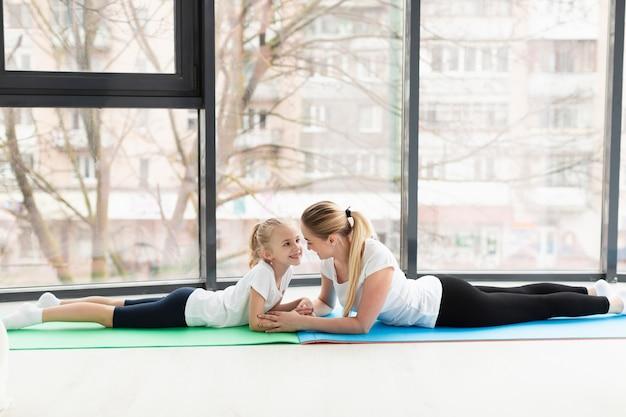 Vista laterale della madre e del bambino sulla stuoia di yoga a casa Foto Gratuite