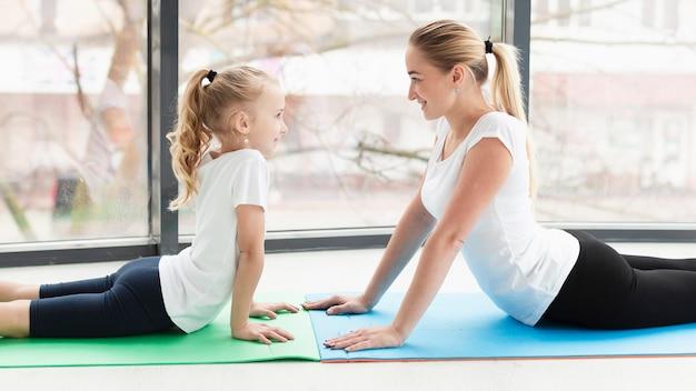 Vista laterale della madre sulla stuoia di yoga a casa con la figlia Foto Gratuite