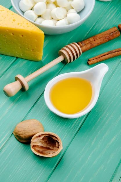 Vista laterale della mozzarella con un pezzo di formaggio olandese con noci di miele e bastoncini di cannella su legno verde Foto Gratuite