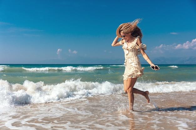 Vista laterale della ragazza allegra che gioca con le onde sulla spiaggia sabbiosa Foto Premium