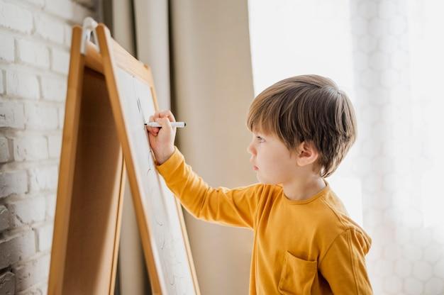 Vista laterale della scrittura del bambino a casa sulla lavagna Foto Gratuite