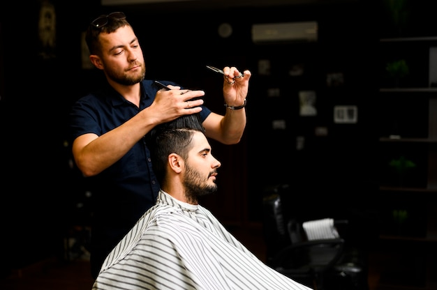 Vista laterale della stilista dando un taglio di capelli Foto Gratuite