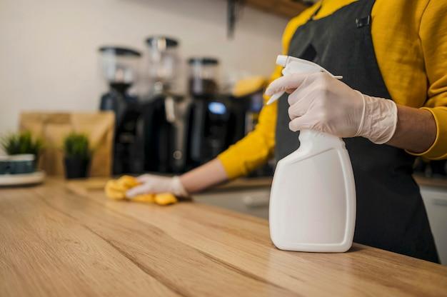 Vista laterale della superficie di pulizia del barista Foto Gratuite