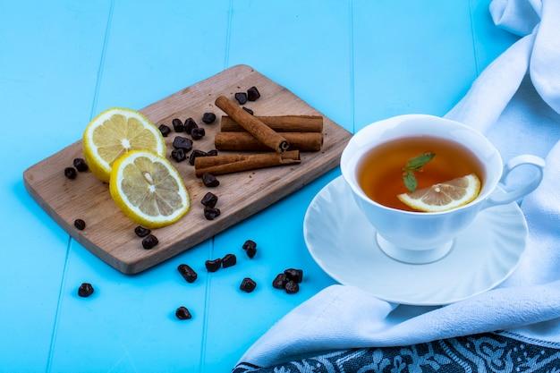Vista laterale della tazza di tè con la fetta di limone sul panno e cannella fette di limone e pezzi di cioccolato sul tagliere su sfondo blu Foto Gratuite