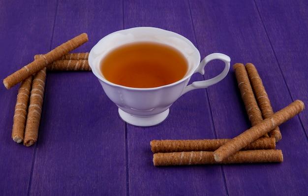 Vista laterale della tazza di tè e bastoncini croccanti su sfondo viola Foto Gratuite