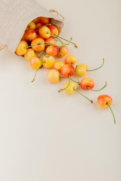 Vista laterale delle ciliege gialle che si rovesciano dal sacco su bianco con lo spazio della copia Foto Gratuite