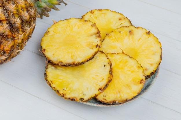 Vista laterale delle fette dell'ananas in piatto con intero su fondo di legno Foto Gratuite