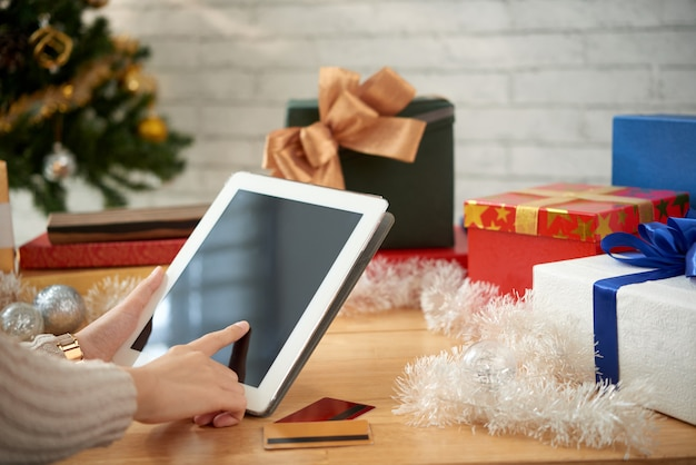 Vista laterale delle mani femminili che comprano i regali per il natale online Foto Gratuite
