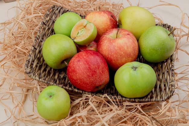 Vista laterale delle mele nel cestino piatto su paglia su avorio Foto Gratuite