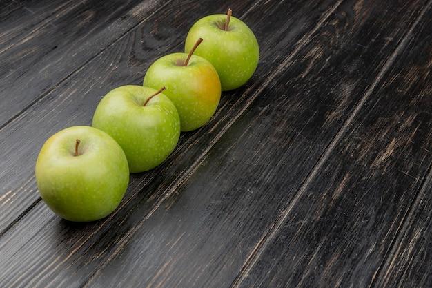 Vista laterale delle mele verdi su superficie di legno Foto Gratuite