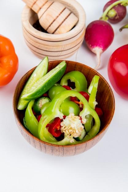 Vista laterale delle verdure come peperoni e cetriolo affettati con il ravanello e pomodoro con pepe nero in frantoio dell'aglio sulla tavola bianca Foto Gratuite