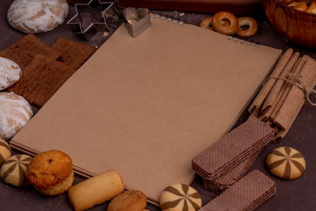 Vista laterale dello sketchbook con differenti biscotti intorno ai muffin del pan di zenzero cialde croccanti del cioccolato su oscurità Foto Gratuite