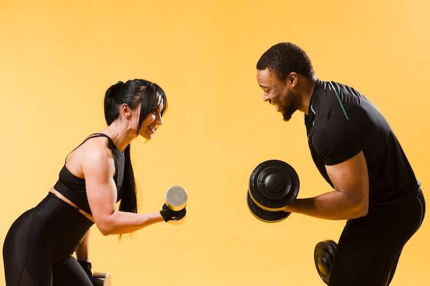 Vista laterale di atleti in possesso di pesi Foto Gratuite