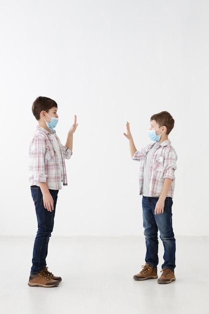 Vista laterale di bambini con maschere mediche che si salutano Foto Gratuite