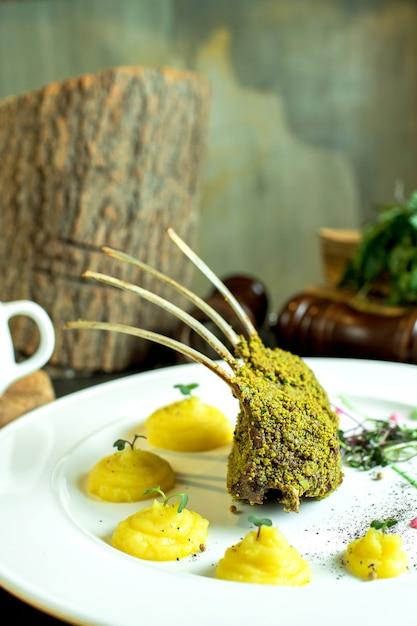 Vista laterale di costolette di agnello arrosto con purè di patate sul piatto Foto Gratuite