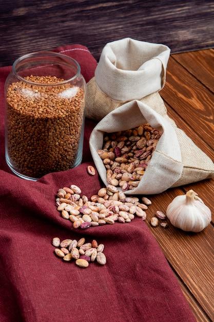 Vista laterale di diversi tipi di legumi in sacchi e grano saraceno crudo in un barattolo di vetro sul tavolo di legno Foto Gratuite