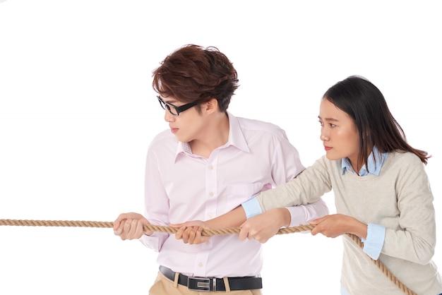 Vista laterale di due asiatici che giocano al tiro alla fune Foto Gratuite