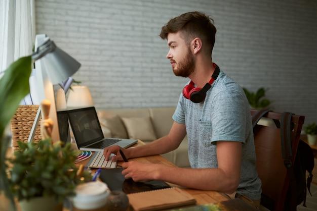 Vista laterale di giovane studente che fa i compiti per la classe di progettazione Foto Gratuite