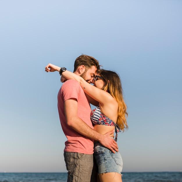 Vista laterale di giovani coppie romantiche che si levano in piedi contro il cielo blu alla spiaggia Foto Gratuite
