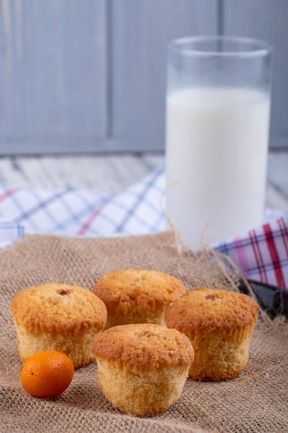 Vista laterale di muffin e un bicchiere di latte sul tavolo Foto Gratuite