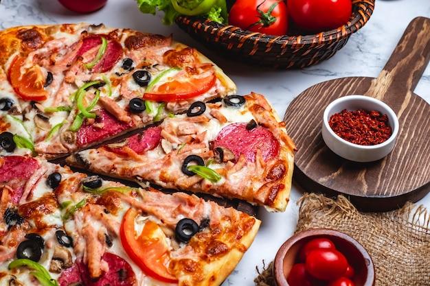 Vista laterale di pizza con salame prosciutto peperoni pomodori verdi olive nere e formaggio sul tavolo Foto Gratuite
