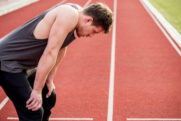 Vista laterale di un corridore maschio velocista sulla pista dopo la corsa Foto Gratuite