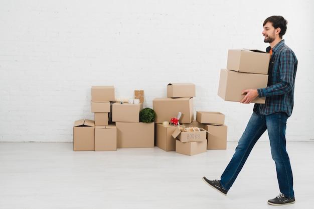 Vista laterale di un giovane che porta le scatole di cartone a disposizione che cammina nella sala Foto Gratuite