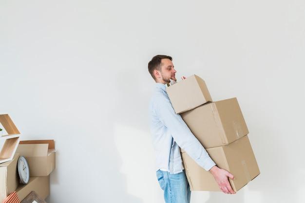 Vista laterale di un giovane che trasporta la pila di scatole di cartone contro il muro bianco Foto Gratuite