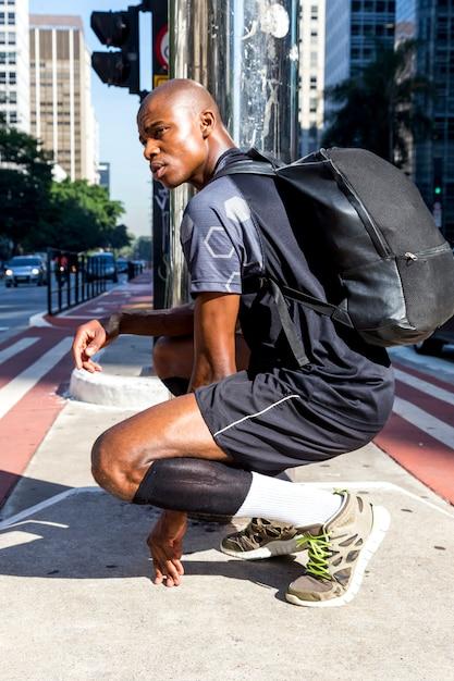 Vista laterale di un giovane sportivo uomo africano con il suo zaino accovacciato in mezzo alla strada Foto Gratuite