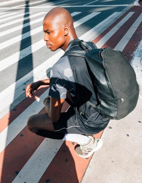Vista laterale di un giovane uomo in buona salute africano con il suo zaino che si accovaccia sulla strada in città Foto Gratuite