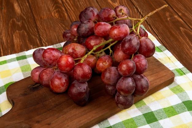 Vista laterale di un grappolo d'uva su una tavola di legno sul tavolo rustico Foto Gratuite