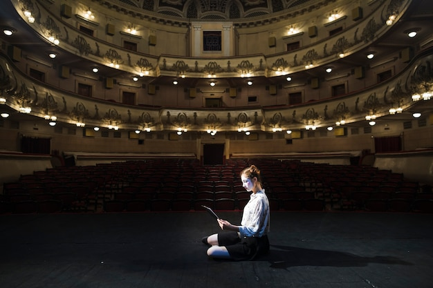 Vista laterale di un manoscritto della lettura del mimo femminile in auditorium vuoto Foto Gratuite