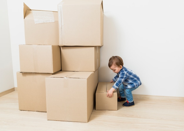 Vista laterale di un piccolo bambino che trasportano le scatole di cartone dal pavimento Foto Gratuite