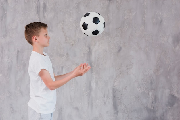 Vista laterale di un ragazzo che gioca con il pallone da calcio contro il contesto concreto Foto Gratuite