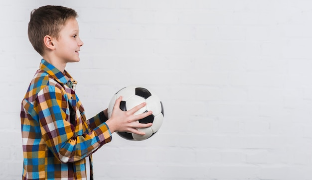 Vista laterale di un ragazzo che tiene calcio in mano in piedi contro il muro di mattoni bianchi Foto Gratuite