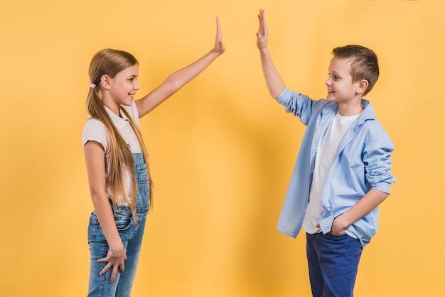 Vista laterale di un ragazzo e una ragazza dando il cinque a vicenda in piedi contro il contesto giallo Foto Gratuite