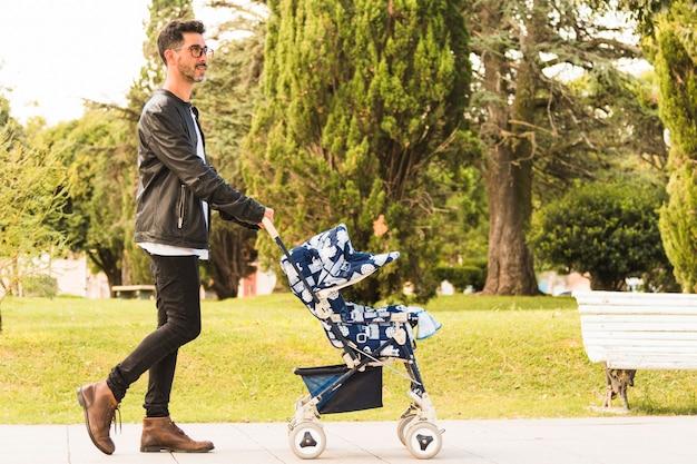 Vista laterale di un uomo che cammina con passeggino nel parco Foto Gratuite