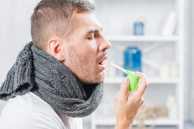 Vista laterale di un uomo che schizza gola con spray Foto Gratuite