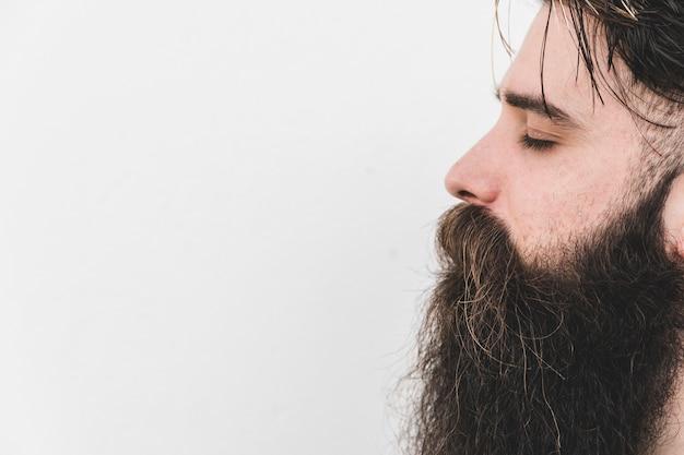 Vista laterale di un uomo con la barba lunga che chiude l'occhio sullo sfondo bianco Foto Gratuite