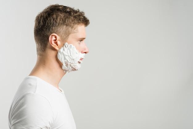 Vista laterale di un uomo con la schiuma da barba sulle guance isolate su sfondo grigio Foto Gratuite
