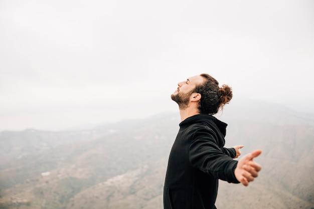 Vista laterale di un uomo spensierato che gode della libertà con le braccia tese Foto Gratuite