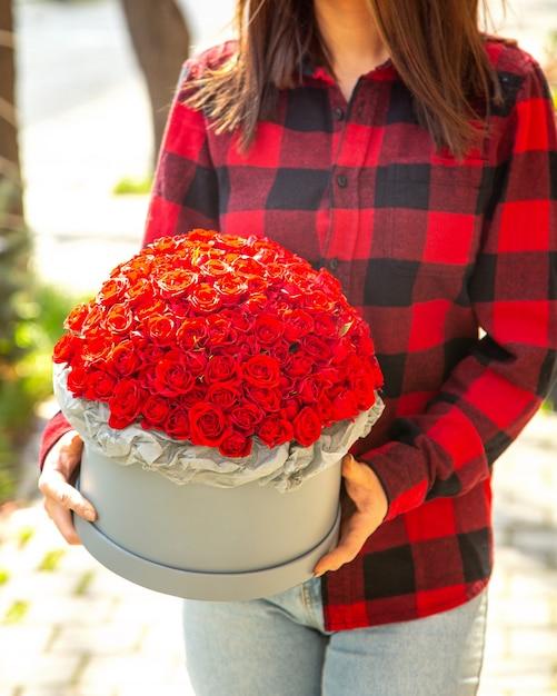 Vista laterale di una donna che tiene una composizione di rose di colore rosso in scatola Foto Gratuite