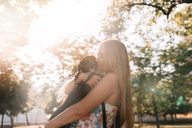 Vista laterale di una giovane donna che bacia il suo cane in giardino Foto Gratuite