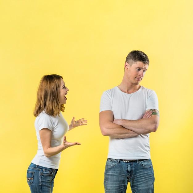 Vista laterale di una giovane donna che rimprovera al suo fidanzato contro sfondo giallo Foto Gratuite