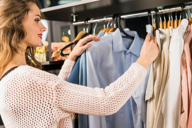 Vista laterale di una giovane donna che sceglie i vestiti sullo scaffale in uno showroom Foto Gratuite