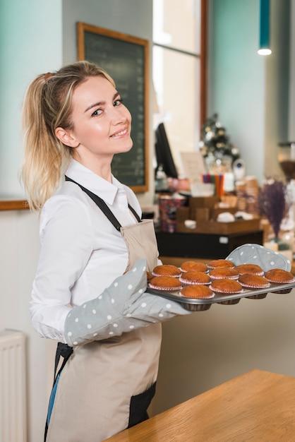 Vista laterale di una giovane donna con vassoio di muffin appena sfornati Foto Gratuite